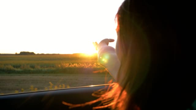 Pretty Young Caucasian Woman In Car And Hand Playing In The Air At Sunset Rays Pretty brunette woman in the car in the passenger seat, put out her hand in the open window, hand playing in the air. Rays of setting sun, shining through the fingers. Wind ruffles hair. Slow motion leaning stock videos & royalty-free footage