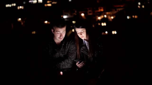 Pretty Young Couple Smiling and Using Smartphone, Sightseeing, Europe, City Break, Romance, Social Media, Tourists, Enjoyment, Night, Portrait, Blurred City Lights Background, Travel, Exploration, Outdoors, Generation Z, Springtime, Vacations