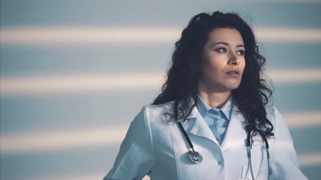 vídeos de stock, filmes e b-roll de doutor consideravelmente da rapariga. durante este tempo, ela tem um phonendoscope no pescoço. durante isso, ela tira os óculos, fecha os olhos da dor de cabeça. - relevo