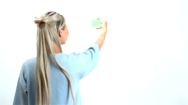 Pretty young girl holding mobile phone Green screen video