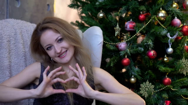 Pretty young girl making a heart with her hands on christmas tree background video