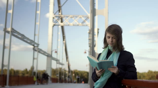 Pretty young girl read book on the bridge video