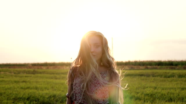 Pretty young hippie woman with a camera on her shoulder walking through an field at sunset