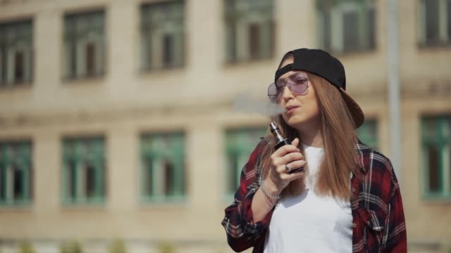 Pretty young hipster woman in black cap vape ecig. Girl vape popular ecig gadget, vaping device.Happy brunette vaper girl with e-cig. Portrait of smoker female model with electronic cigarette vaporizer. Slow motion shot