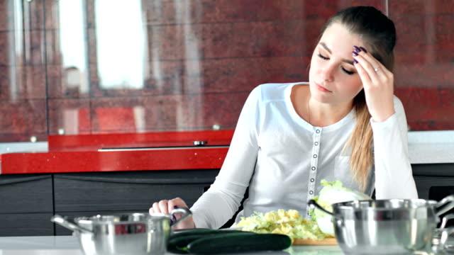 vidéos et rushes de jolie jeune femme au foyer est fatigué cuisine salade dans la cuisine - diététique