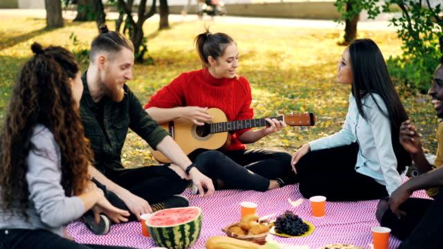 vídeos de stock, filmes e b-roll de bela jovem está tocando guitarra, enquanto seus amigos estão cantando e ouvindo música repousando sobre xadrez no parque. pastelaria e alimentos frutas são visíveis no cobertor. - música acústica