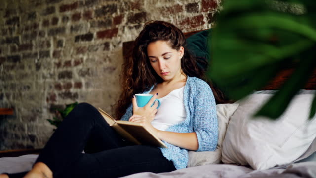 Pretty young lady is reading book in bed holding cup of tea and resting on pillows enjoying day at home. Beautiful loft style apartment with wooden furniture and plants is visible. Pretty young lady is reading book in bed holding cup of tea and resting on comfy pillows enjoying calm day at home. Beautiful loft style apartment with wooden furniture and plants is visible. resting stock videos & royalty-free footage