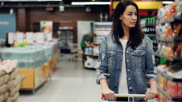 Pretty young lady is walking through aisle in supermarket with shopping cart looking at shelves with products, employees in uniform are working in background. Pretty young lady is walking through aisle in spacious supermarket with shopping cart looking at shelves with products, employees in uniform are working in background. woman pushing cart stock videos & royalty-free footage
