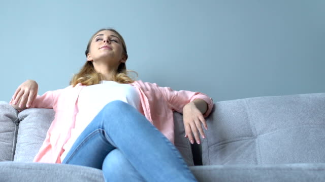 pretty ung dam sitter på soffan och avkopplande, känna sig nöjd med renovering - kvinna ventilationssystem bildbanksvideor och videomaterial från bakom kulisserna