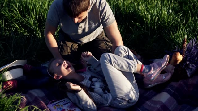 pretty young man in park with his little children having fun. playing with girls. they lie on the grass, laugh, their dad tickles them. happy family time in nature - fare il solletico video stock e b–roll