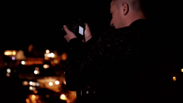 Pretty Young Man Smiling and Using Smartphone, Sightseeing, Europe, City Break, Romance, Social Media, Tourist, Enjoyment, Night, Portrait, Blurred City Lights Background, Travel, Exploration, Outdoors, Generation Z, Springtime, Vacations