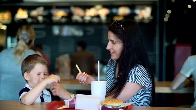 꽤 젊은 어머니와 패스트 푸드를 먹는 아이 - burger and chicken 스톡 비디오 및 b-롤 화면