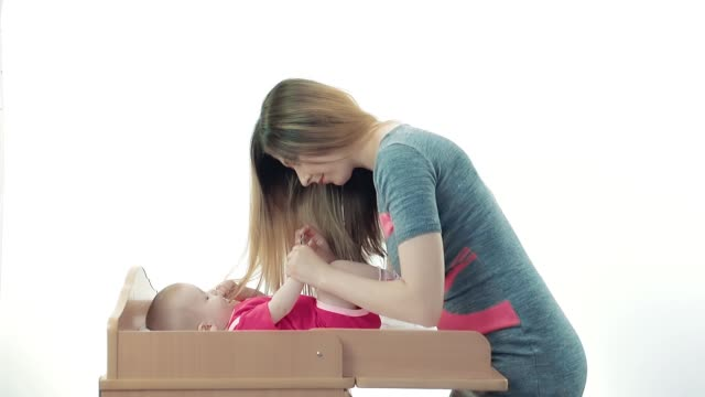 Pretty young mother cuts nails her baby