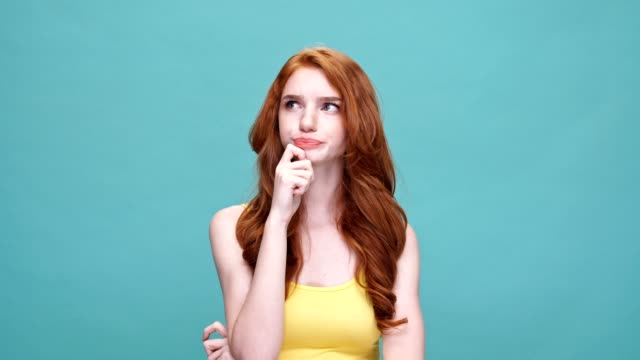 Pretty young redheaded girl stretching hands and yawning in the morning isolated over blue background video