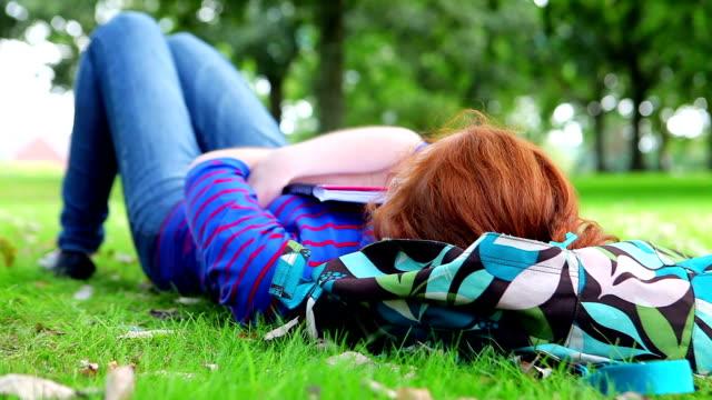piuttosto giovane studente sdraiato su un la cartella - sonnecchiare video stock e b–roll