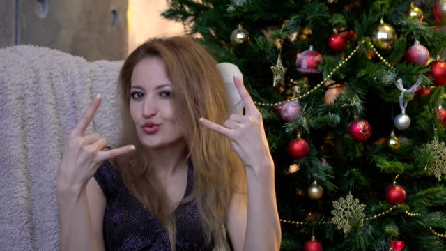 pretty young woman doing rock gesture on christmas tree background video