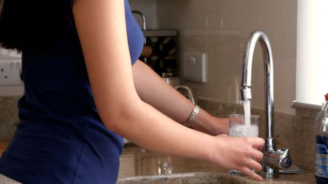 Pretty young woman drinking water in the kitchen Side view of a pretty young woman drinking water in the kitchen faucet stock videos & royalty-free footage