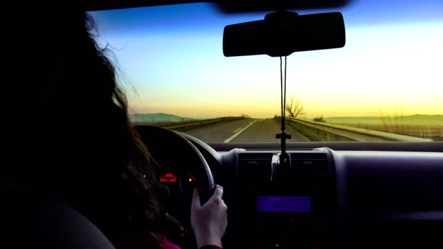 pretty, young woman driving her modern car at sunset video