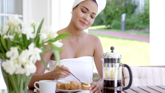 Pretty young woman eating breakfast on a patio Pretty young woman eating breakfast on an outdoor patio in a fresh white towel smiling with pleasure as she prepares her food wearing a towel stock videos & royalty-free footage
