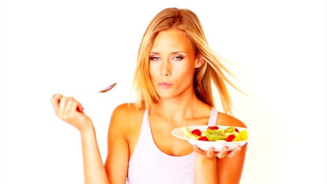 vídeos de stock, filmes e b-roll de bela jovem comendo salada de frutas - fruit salad