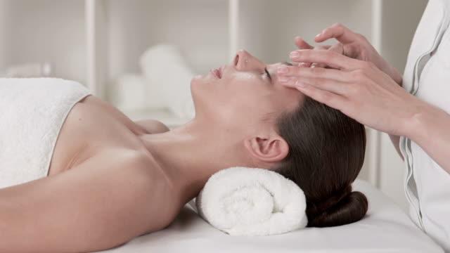 vídeos y material grabado en eventos de stock de dolly hd: hermosa mujer joven disfruta de un masaje facial - tratamiento de spa