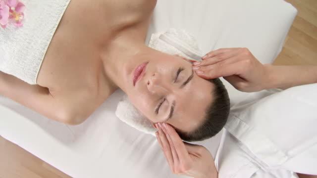 vídeos y material grabado en eventos de stock de grulla de alta definición: hermosa mujer joven disfruta de un masaje relajante, tratamiento facial - tratamiento de spa