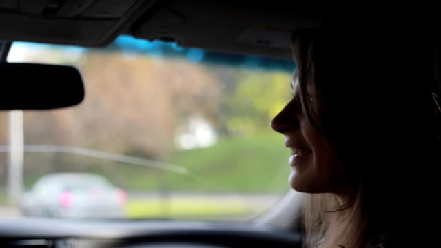 Pretty young woman in a car on the go in a city in autumn. She talks and smiles, looks out of window of the car video