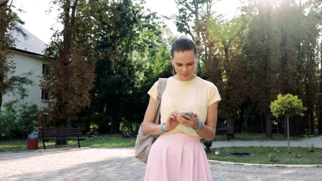 Pretty young woman in a pink skirt and a yellow T-shirt uses a smart phone in the park on a sunny day video