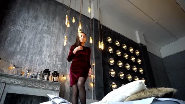 Pretty young woman in dress standing on bed and poses in studio Pretty young woman in dress standing on bed and poses in studio. double bed stock videos & royalty-free footage