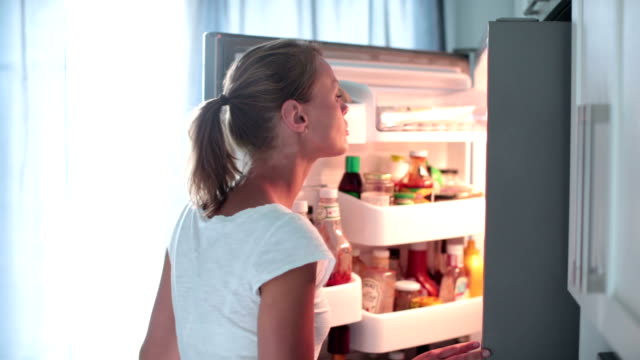 Pretty young woman opening the fridge Pretty young woman opening the fridge in her modern kitchen, taking a box with food, controlling the expiratory date fridge stock videos & royalty-free footage