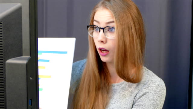 vidéos et rushes de jolie jeune femme assis au bureau dans le bureau, parler avec quelqu'un via appel vidéo sur ordinateur - twerk