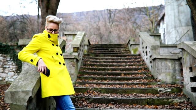 vídeos y material grabado en eventos de stock de bastante joven mujer sentada en una escalera con teléfono móvil - moda de otoño