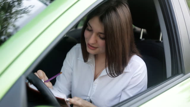 hübsche junge frau auf ihr auto zu sitzen und sich notizen macht, um ihr tagebuch. herbst-saison-stimmung. - teurer lebensstil stock-videos und b-roll-filmmaterial