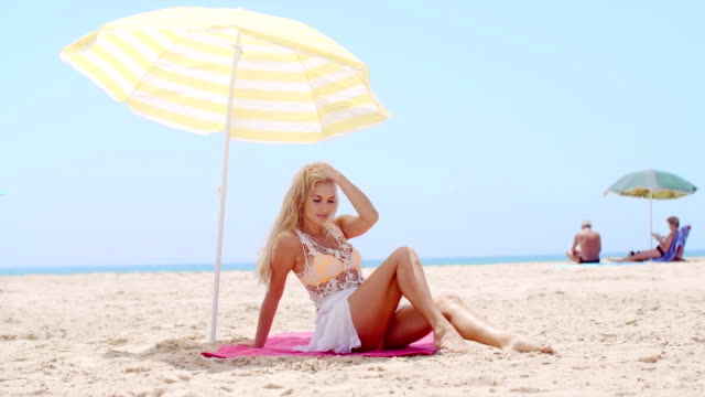Pretty Young Woman Sitting Under Beach Umbrella video
