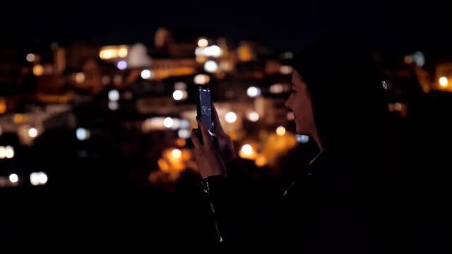 Pretty Young Woman Smiling and Using Smartphone, Sightseeing, Europe, City Break, Romance, Social Media, Tourist, Enjoyment, Night, Portrait, Blurred City Lights Background, Travel, Exploration, Outdoors, Generation Z, Springtime, Vacations