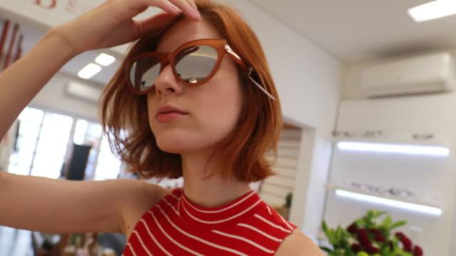hübsche junge frau versucht, auf modische sonnenbrille - sonnenbrille stock-videos und b-roll-filmmaterial