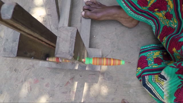 Pretty young woman turns spindle and spinning wheel FIlmed in a village in Bengal, India sari stock videos & royalty-free footage