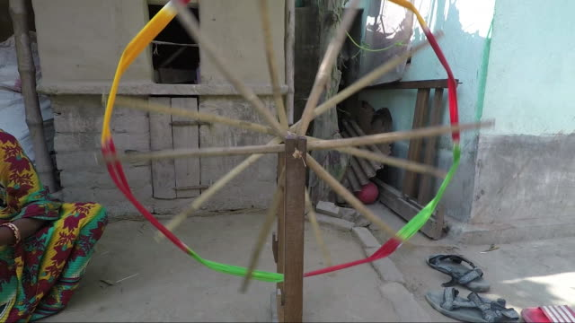 Pretty young woman turns spindle and spinning wheel track out from spinning wheel to medium shot.  2X slow motion. Bengal, India sari stock videos & royalty-free footage