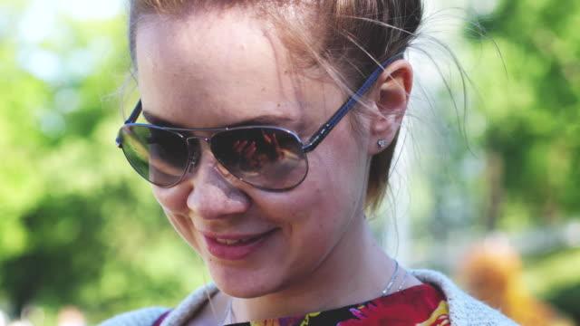 vidéos et rushes de jolie jeune femme portant lunettes de soleil souriant profitant de la lumière du soleil sur la nature. 3840 x 2160 - rouge à lèvres rouge