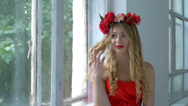 Pretty young woman with wreath of red flowers on her head sitting on windowsill, smiling, slow motion video