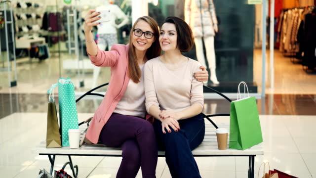 vídeos de stock, filmes e b-roll de mulheres muito jovens estão tomando selfie usando a câmera do smartphone, sentado no banco em shopping e se divertindo. conceito moderno de tecnologia, lojas e amigos. - shopping center