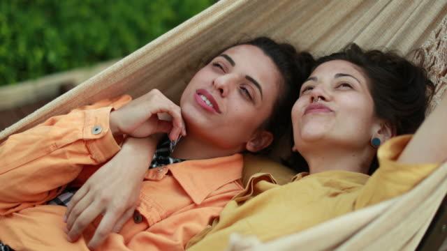 stockvideo's en b-roll-footage met lhbt-trots. lesbische relatie samen rusten en knuffelen. vriendinnen die de hemel op hangmat bekijken - daten
