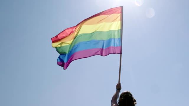 vídeos de stock, filmes e b-roll de bandeira do arco-íris do orgulho lgbt que acena no movimento lento durante uma parada do orgulho - homossexualidade