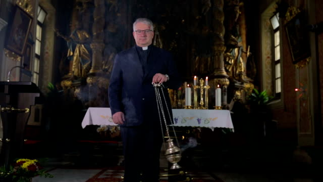 priest in the middle of the smoking ritual - katoliklik stok videoları ve detay görüntü çekimi