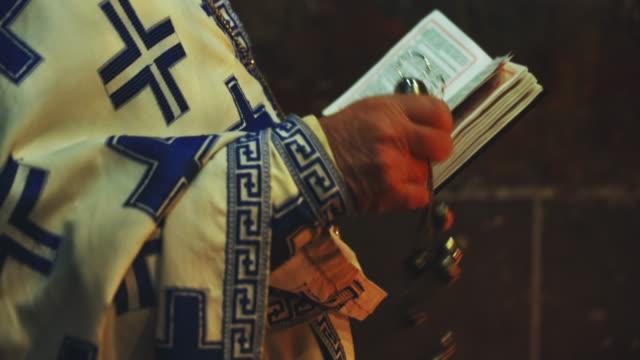 stockvideo's en b-roll-footage met een priester van de kerk die een psalmboek leest, dat een vakantiedienst, gebed uitvoert. de priester zwaait een thurmon - heilig geschrift