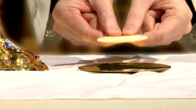 vídeos y material grabado en eventos de stock de sacerdote lugares eucharist en placa - misa