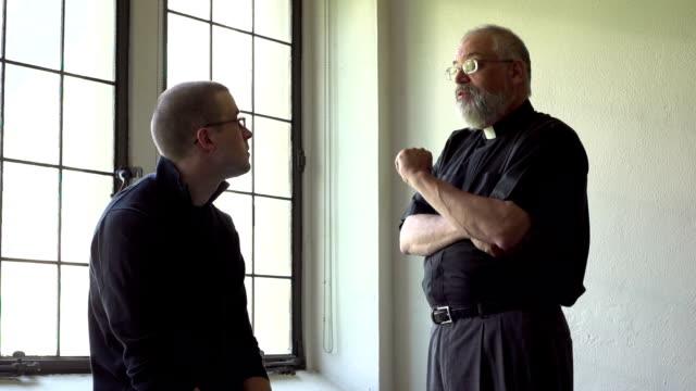 Sacerdote hablar con parishioner en una iglesia - vídeo