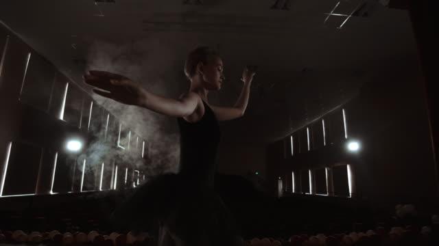 プリマ・バレリーナは、オペラとバレエ劇場で重要な公演を行う前に、夜遅くにスポットライトを浴びてステージ上でトレーニングを行います。屋内 - オペラ点の映像素材/bロール