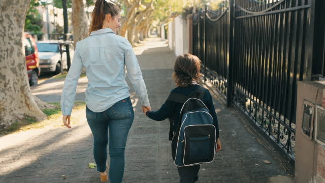 primary school student walking to school with mother - children video stock e b–roll