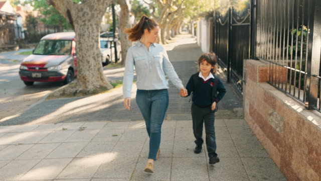Primary School Student Walking to School with Mother Primary School Student Walking to School holding his mother hand mid adult women stock videos & royalty-free footage